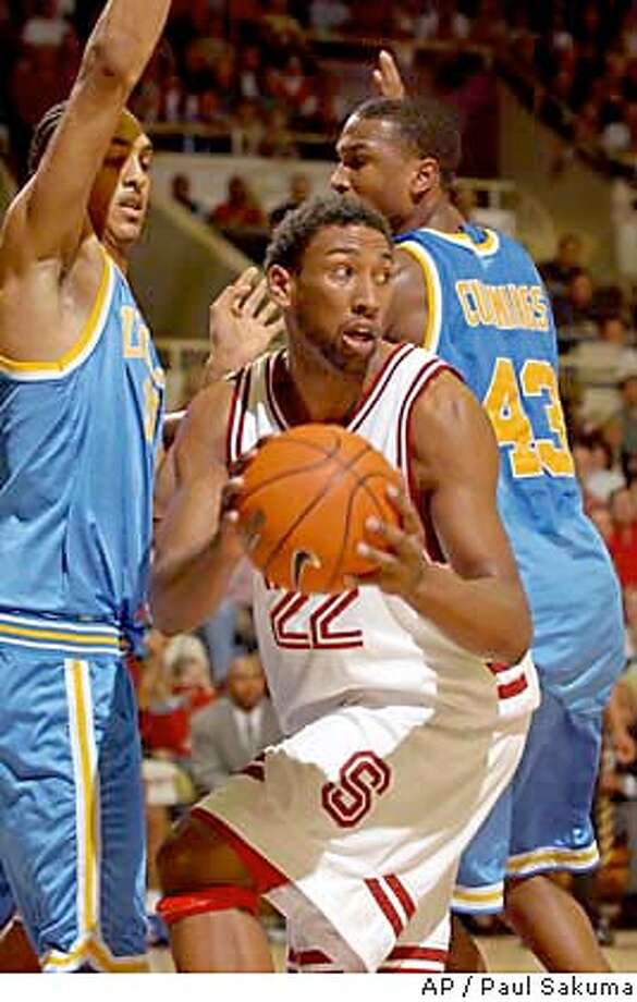 Stanford forward Justin Davis is closely guarded by UCLA center Ryan Hollins, left, and forward T.J. Cummings, in the first half, Thursday, Jan. 22, 2004, in Stanford, Calif. Stanford defeated UCLA, 67-52. Davis was high-scorer with 21 points. (AP Photo/Paul Sakuma) Photo: PAUL SAKUMA
