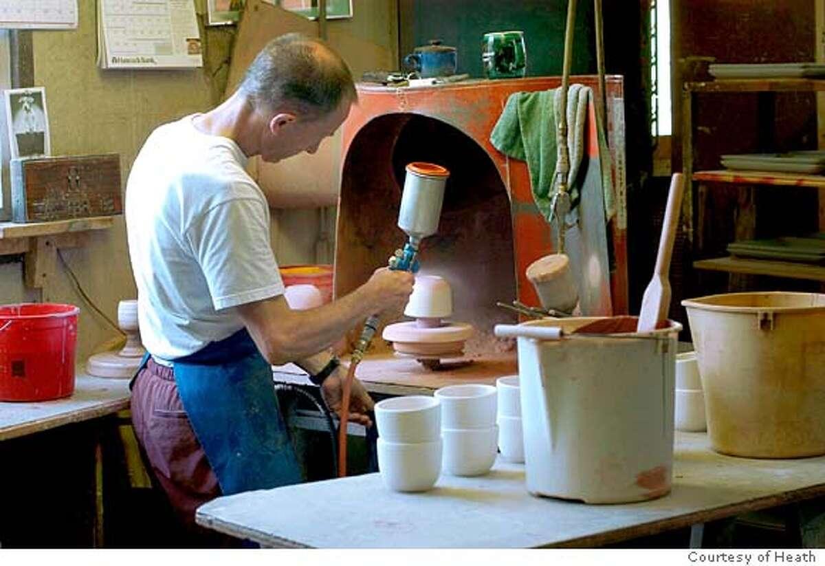 glazes being sprayed onto fired bowls.