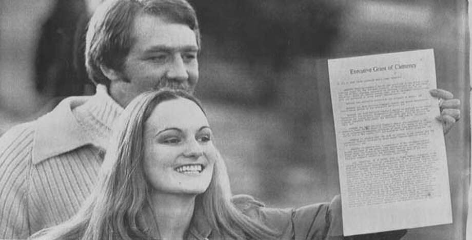 2/1/79: Patricia Hearst waves the presential commutation order for photographers as she leaves the Federal Corrections Institution in Pleasanton early Thursday morning. With her is fiance Bernard Shaw.