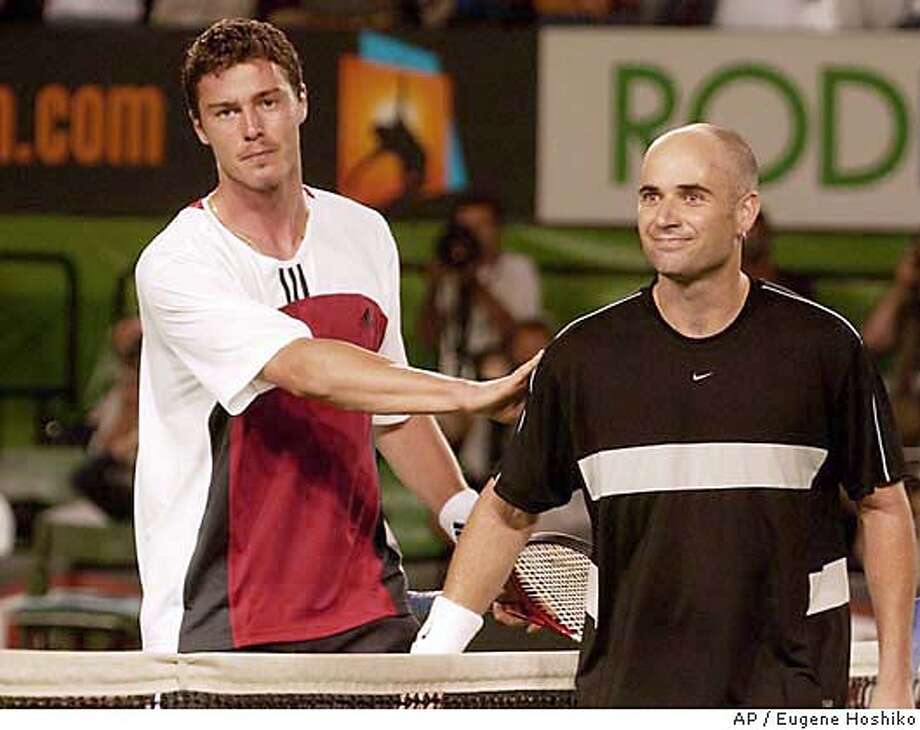 Russia's Marat Safin, left, pats Andre Agassi of the U.S. on the shoulder after their semifinal match at the in Melbourne, Australia, Thursday, Jan. 29, 2004. Safin won in five sets 7-6 (6), 7-6 (6), 5-7, 1-6, 6-3. (AP Photo/Eugene Hoshiko) Photo: EUGENE HOSHIKO