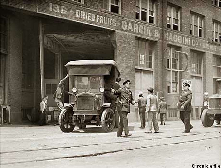 Signal for Actoin! First truck, moving from San Francisco's water front, paralyzed for months as a result of the longshoremen's strike, pictured with police guard at the warehouse at 128 King St. Despie hostility of strikers, much freight was transferred yesterday when port was opened. Photo by Chronicle