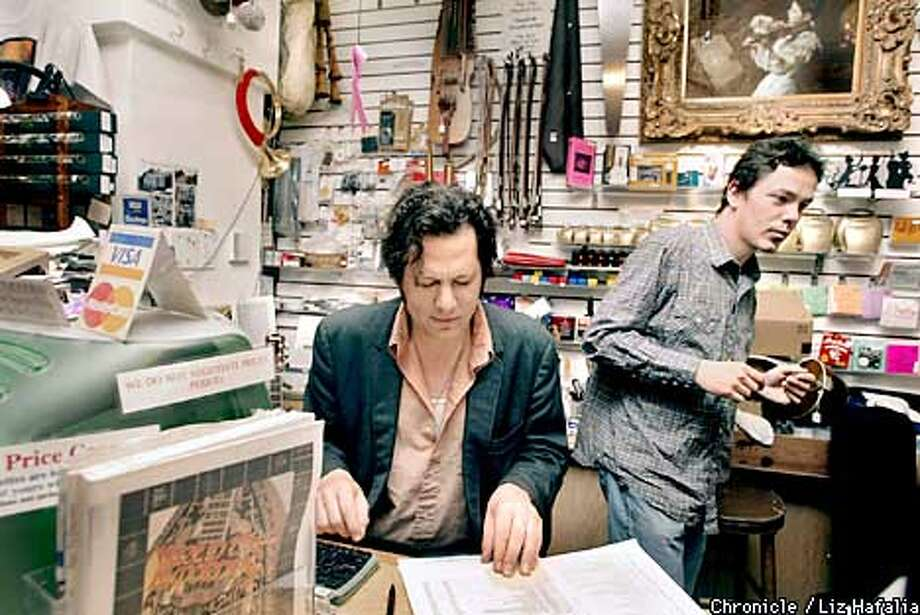 Jeff Lucas takes a look at new inventory for his music shop--Lark In the Morning--while Mark Rodgers waits for customers.  (PHOTOGRAPHED BY LIZ HAFALIA/THE SAN FRANCISCO CHRONICLE) Photo: LIZ HAFALIA