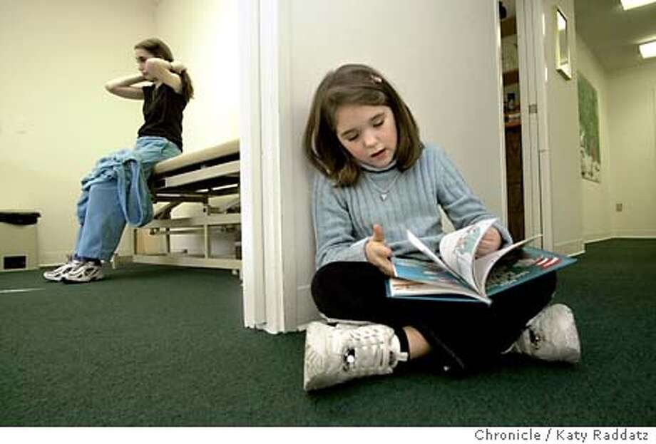 "SHOWN: Patient Andrina Autagne, age 13 (LEFT) waits on the exam table for Dr. Charlotte Thompson not shown) while her little sister Kalie Autagne (cq), age 9, reads ""The Cat in the Hat"" in the hallway. The Center for Handicapped Children and Teenagers will close at the end of January, 2004 because of funding problems. Dr. Charlotte Thompson is the only doctor in the area with expertise to care for kids with severe neuromuscular diseases. Writer is Kathy Seligman; this shoot date is 1/21/04. Katy Raddatz / The Chronicle Photo: Katy Raddatz"