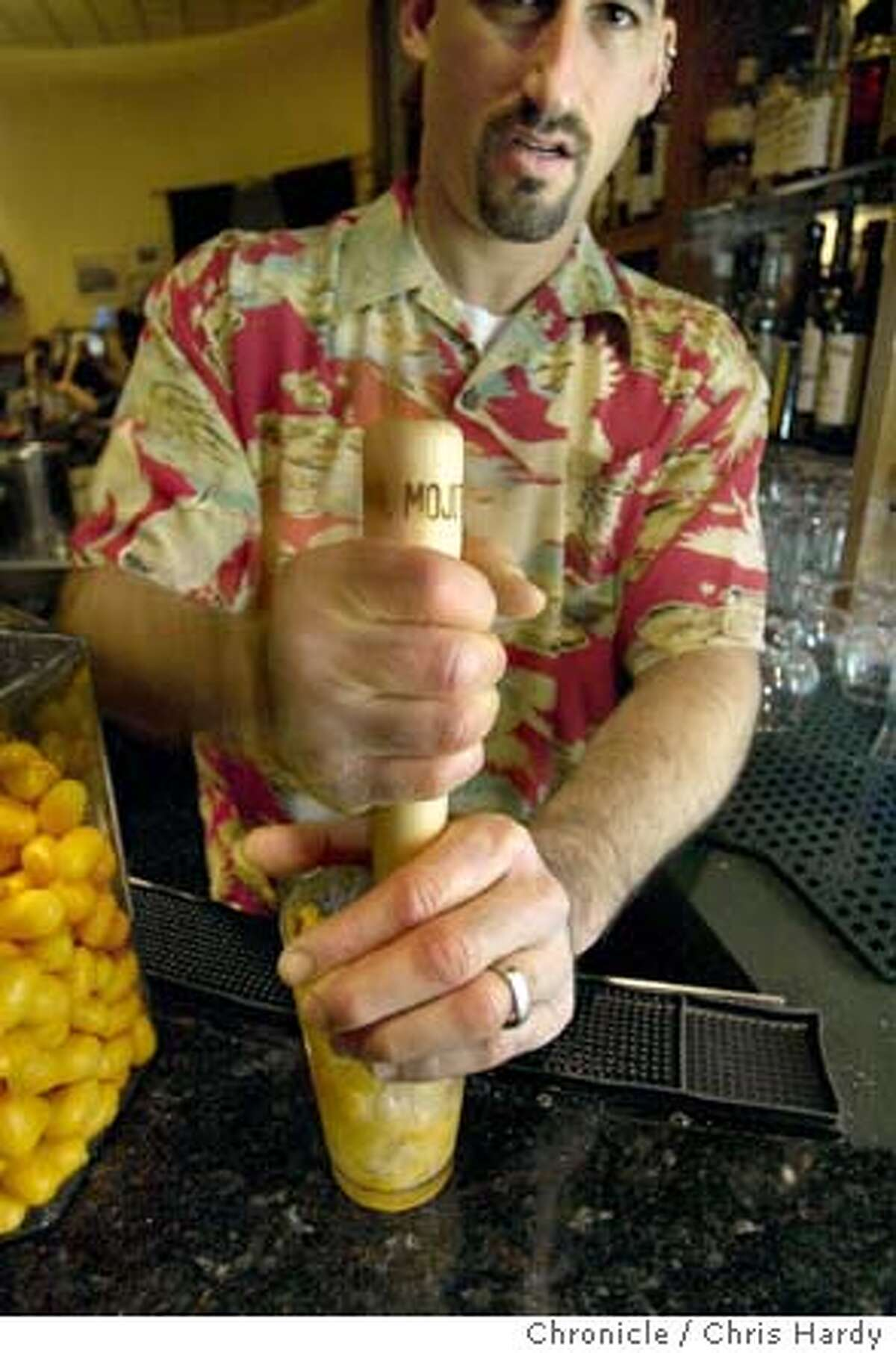"""Enrico's bar manager David Nepove making the Kumquat Caipiroshka """"stick"""" drink - which calls for the ingredients to be muddled together with a wooden muddler, or stick. CHRIS HARDY / The Chronicle"""