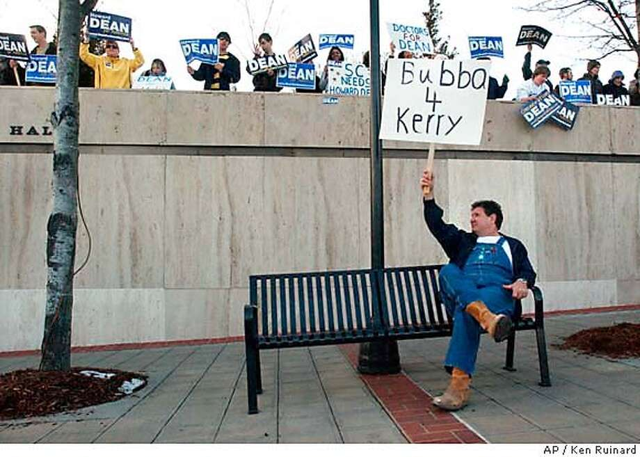 Dan Dearybruy of Cowpens, S.C., below, sits holding a sign supporting Sen. John Kerry, D-Mass., as supporters of one of Kerry's fellow Democratic presidential hopefuls Howard Dean stand on a walkway above, on Main Street in Greenville, S.C., Thursday, Jan. 29, 2004. The sign waving took place across from the Peace Center concert hall, where Democrats running for president met to debate Thursday night. The South Carolina primary is Tuesday. (AP Photo/Anderson Independent Mail, Ken Ruinard) Photo: KEN RUINARD