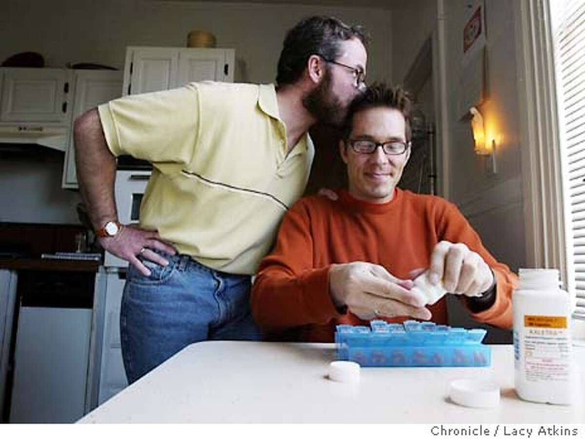 HOUSING_015_.jpg Brian Basinger gently kisses his partner James Nykolay as he fills his medicine counter with AIDS medication. Jan. 21, 2004, in San Francisco. Lacy Atkins / The Chronicle