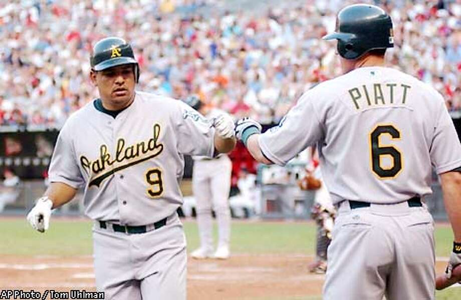 Oakland Athletics' Olmedo Saenz gets congratulated by teammate Adam Piatt after hitting a home run in the third inning against Cincinnati Reds pitcher Bruce Chen at Cinery Field in Cincinnati Saturday June 22, 2002. (AP Photo Tom Uhlman) Photo: TOM UHLMAN