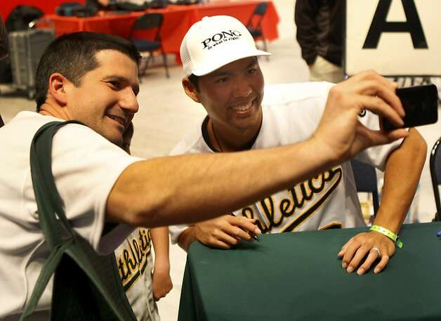 Kurt Suzuki (right) smiled as he posed with a fan. The Oakland A's held their annual FanFest at the Oakland Arena Sunday January 29, 2012 to delight of their fans. Photo: Sean Culligan, The Chronicle