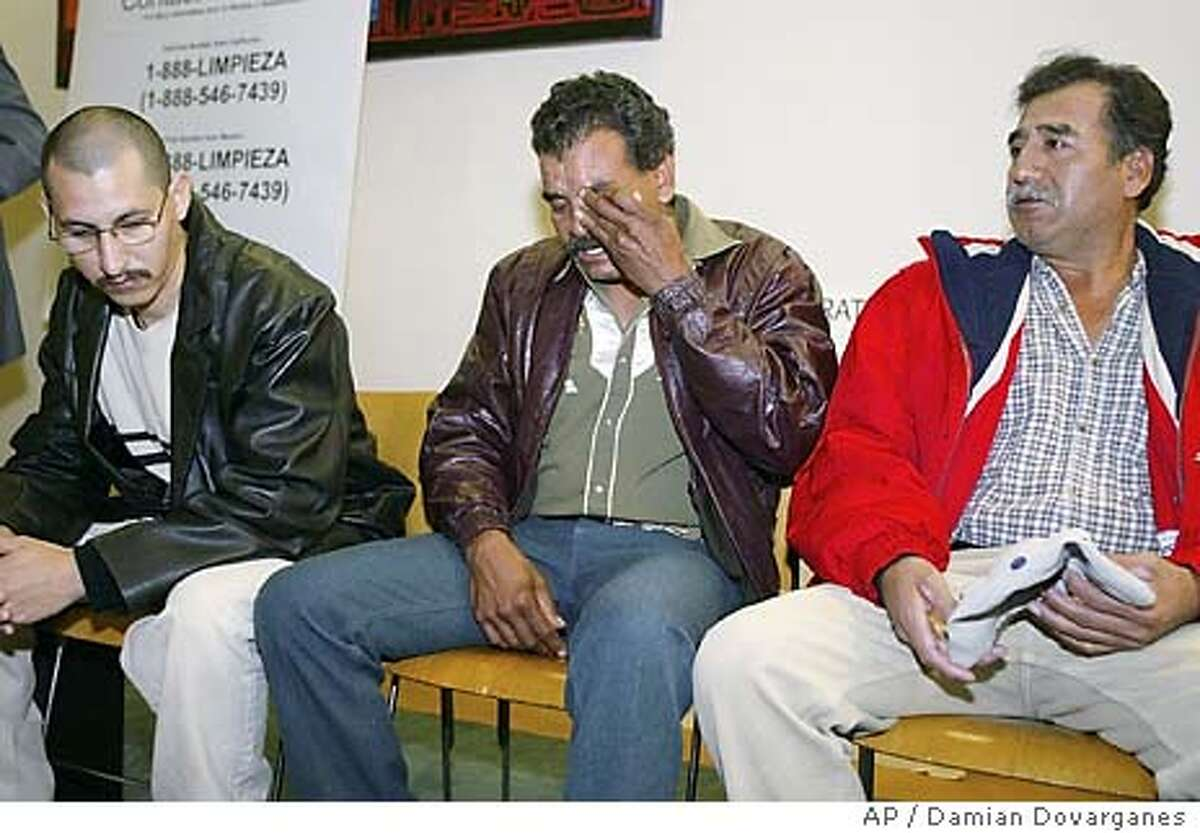 Immigrant worker Hipolito Soto, middle, cries after describing his former job conditions as a janitor at Vons supermarket, Tuesday, Jan. 27, 2004, during a news conference at the Mexican American Legal Defense and Education Fund (MALDEF) in Los Angeles. Soto is one of thousands of janitors joining in a federal class-action lawsuit several supermarkets and temporary work agencies over unpaid wages and unfair labor business practices. Soto was joined by former co-workers, Jesus, left, and Issaias. Both declined to give their last names. (AP Photo/Damian Dovarganes)