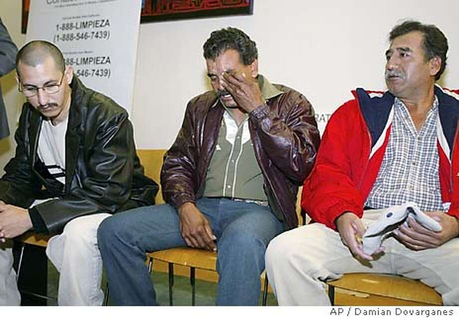 Immigrant worker Hipolito Soto, middle, cries after describing his former job conditions as a janitor at Vons supermarket, Tuesday, Jan. 27, 2004, during a news conference at the Mexican American Legal Defense and Education Fund (MALDEF) in Los Angeles. Soto is one of thousands of janitors joining in a federal class-action lawsuit several supermarkets and temporary work agencies over unpaid wages and unfair labor business practices. Soto was joined by former co-workers, Jesus, left, and Issaias. Both declined to give their last names. (AP Photo/Damian Dovarganes) Photo: DAMIAN DOVARGANES