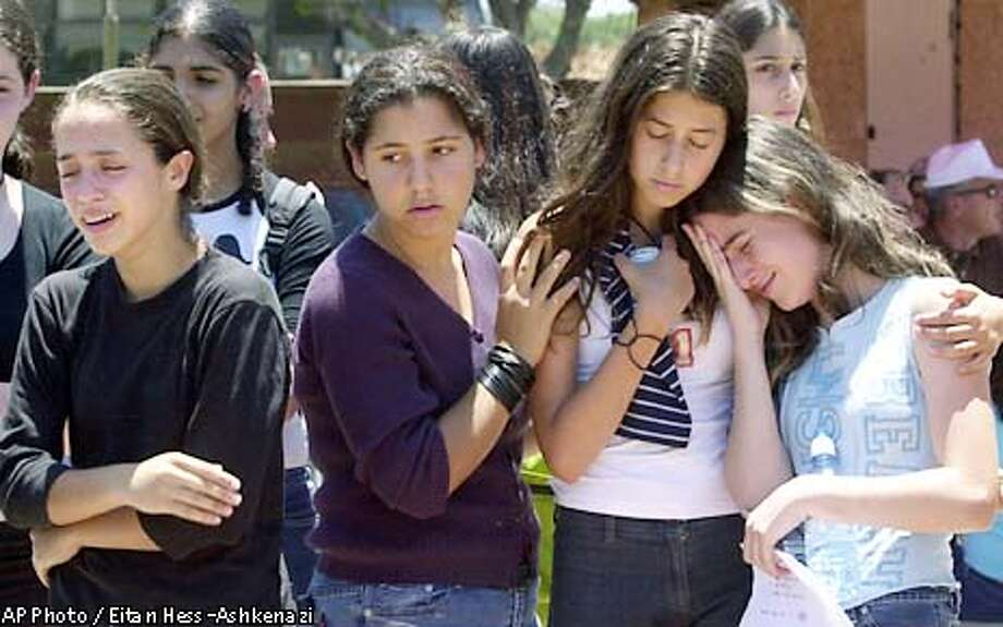 Unidentified friends of Hadar Hershkovitz cry after her funeral in the coastal city of Herzeliya near Tel Aviv, Israel, Wednesday, June 12, 2002. Hrshkovitz was killed Tuesday as a Palestinian bomber blew himself up in a restaurant in the city. (AP Photo/Eitan Hess-Ashkenazi). Photo: EITAN HESS-ASHKENAZI