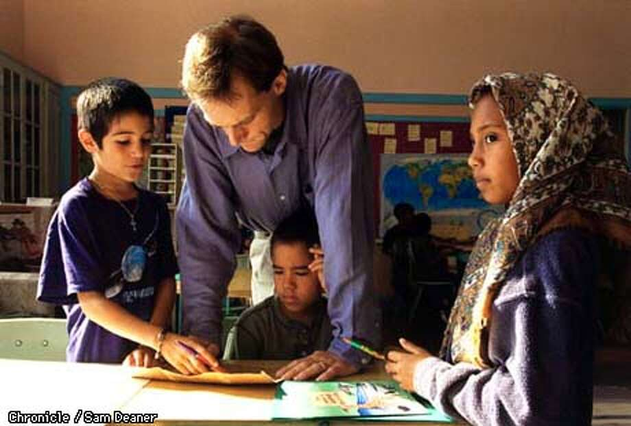 New Viallage School teacher Jonathan Bartlett helps pupils with maps during group time Wednesday. Pictured from left are pupils Lucas Briffa, Jeremy Bowles and Saqifa Minyoka Brown. (CHRONICLE PHOTO BY SAM DEANER) Photo: SAM DEANER