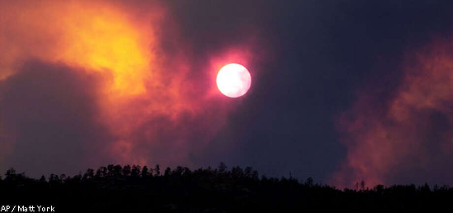 Smoke from the Rodeo Fire crosses in front of the sun outside Show Low, Ariz., Wednesday, June 19, 2002. What started out as a small fire on Tuesday ballooned into a 25,000-acre inferno, forcing the evacuation of more than 4,000 people from three communities.(AP Photo/Matt York) Photo: MATT YORK