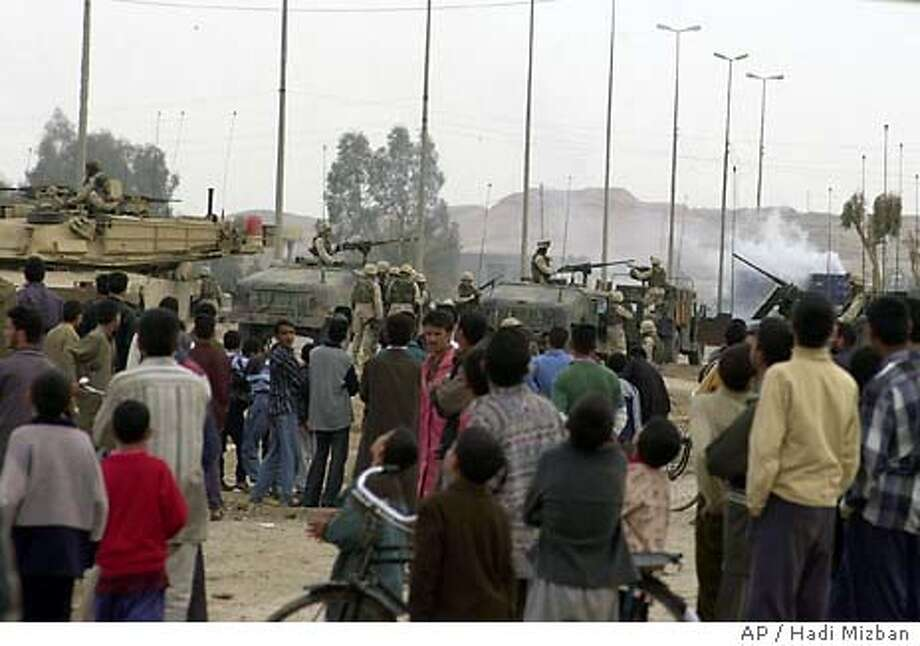 A crowd of Iraqis gather to watch as U.S. troops secure the scene of an explosion near Khaldiyah, Iraq Tuesday Jan. 27, 2004. A roadside bomb exploded next to a passing U.S. military convoy west of Baghdad Tuesday followed by a second bomb when reinforcements arrived, witnesses said. Three American soldiers and two Iraqi civilians were killed. (AP Photo/Hadi Mizban) Photo: HADI MIZBAN