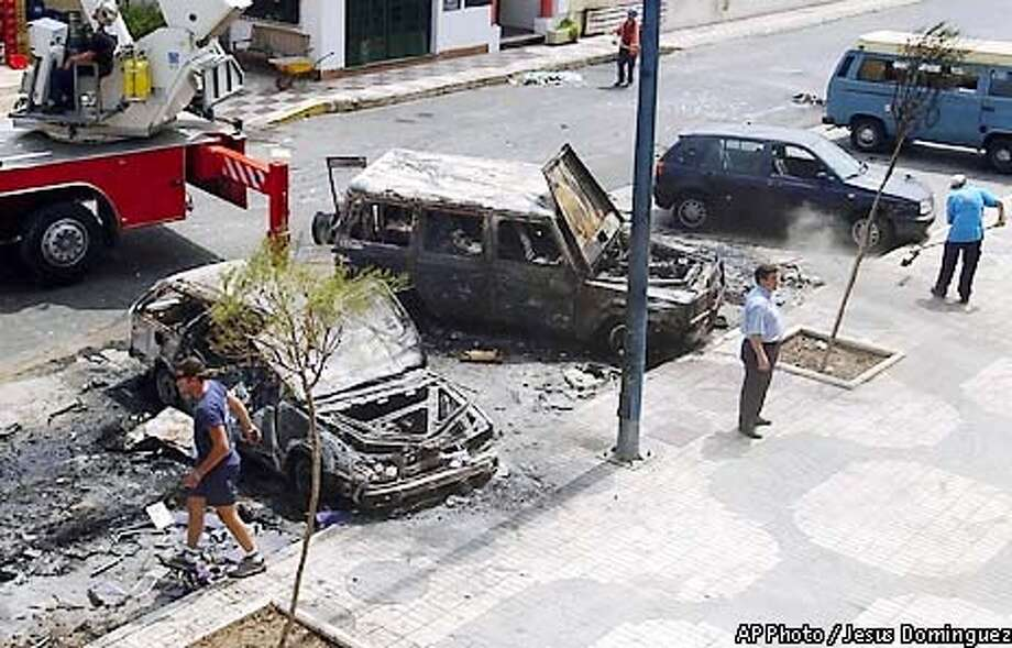 Unidentified men clean around damaged cars at the scene where a car-bomb exploded in the southern coastal resort town of Fuengirola, Spain, Friday June 21, 2002. Six people were reported to be injured in the attack which occurred on the starting day of the EU summit in Seville. (AP Photo/EFE, Jesus Dominguez) ** SPAIN OUT ** Photo: JESUS DOMINGUEZ