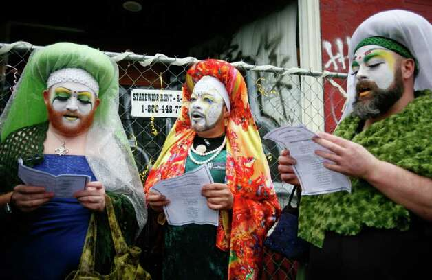 Three Sisters of Perpetual Indulgence sing with other guests during Babylonia Aivaz's wedding to the 10th Ave and Union St. warehouse on Sunday, Jan. 29, 2012. About 30 people attended Aivaz's wedding, which she says is a gay marriage because the building is a woman. Aivaz, who was among the Occupy Seattle protesters who wanted to reclaim it as community space, is using the wedding to protest the demolition of the 107-year-old building. An apartment building will be built in its place. Photo: LINDSEY WASSON / SEATTLEPI.COM