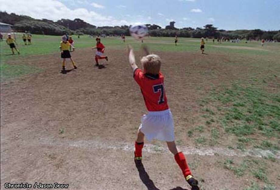 Colin Nicol, 9, #7, brings the ball into play during a soccer match between his team, the Pirates and the Suns at Beach Chalet Soccer Fields Saturday. The fields are a patchwork of turf and dirt despite nearly $30,000 in efforts by the city to resurface the fields. CHRONICLE PHOTO BY JASON M. GROW
