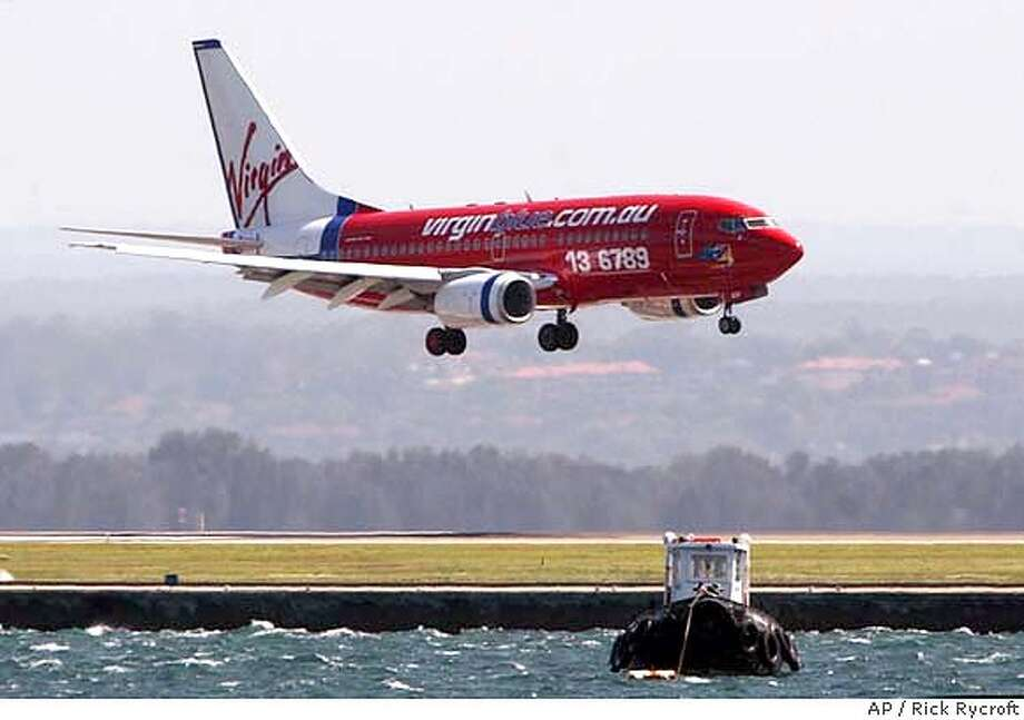A Virgin Blue jet comes into land at Sydney Airport, Thursday, Dec. 18, 2003. The low-cost airline will soon have a competitior in the budget air travel business with Qantas looking to enter the discounting business with their Jet Star branded airline from February, 2004. (AP Photo/Rick Rycroft) Virgin Airlines has started its low-cost Virgin Blue in Australia and is planning to move into the New Zealand market with Pacific Blue Airlines. DEC. 18, 2003 PHOTO Photo: RICK RYCROFT