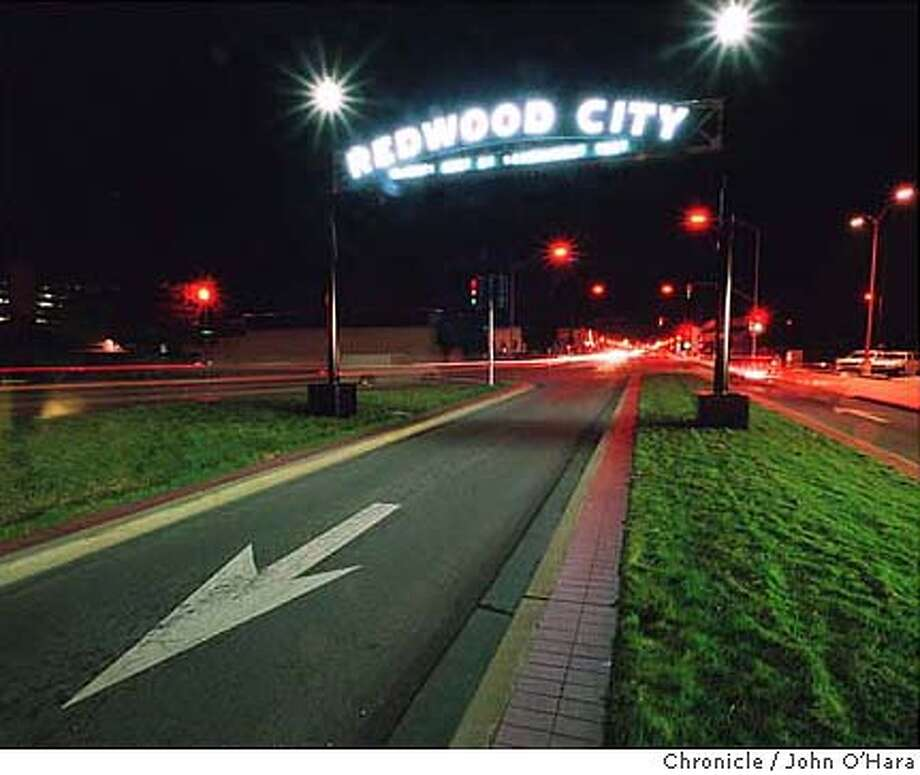 """REDWOOD CITY'S NEW ARCH, IDENTICAL TO THE ONE TORN DOWN IN 1970, WAS INSTALLED TO LIGHT UP BROADWAY IN TIME FOR THE HOLIDAYS. THE ARCH DISPLAYS THE CITY'S SLOGAN, """"CLIMATE BEST BY GOVERNMENT TEST."""" CAT Photo: JOHN O'HARA"""