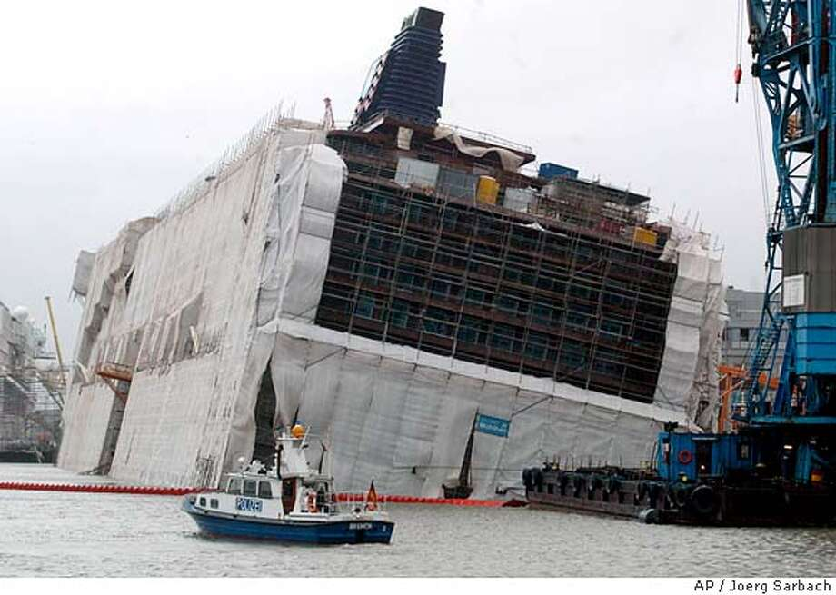 "Scaffolded cruise liner ""Pride of America"" lists at a pier of the Lloyd shipyard in the harbor of Bremerhaven, northwestern Germany, Wednesday, Jan. 14, 2004, after the vessel took on water during a heavy storm overnight causing it to list . The ship is under construction for Norwegian Cruise Line (NCL). Three workers were injured. (AP Photo/Joerg Sarbach) Damaged Pride: Scaffolded Pride of America lists at its German shipyard pier after a heavy storm. Photo: JOERG SARBACH"