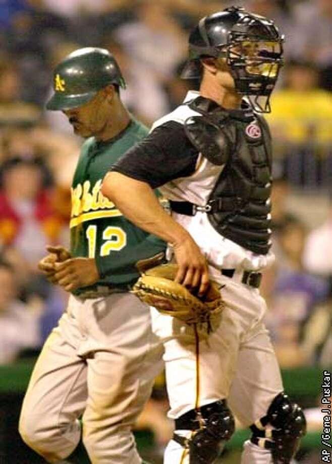 The A's Terrence Long scores the game-winning run behind Pirates catcher Jason Kendall. Associated Press photo by Gene J. Puskar