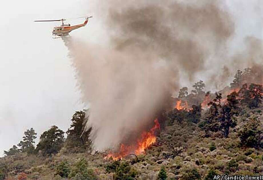 A helicopter drops water on the fire in Walker Canyon near Walker, Calif., on Monday, June 17, 2002. (AP Photo/Reno Gazette-Journal, Candice Towell) Photo: CANDICE TOWELL