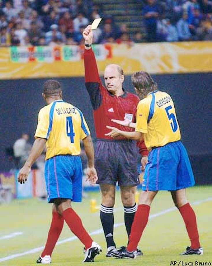 Referee Brian Hall of the United States shows the yellow card to Ecuador's Ulises De La Cruz as Alfonso Obregon pleads for clemency during the 2002 World Cup Group G soccer match between Italy and Ecuador at the Sapporo Dome, Japan, Monday June 3, 2002. The other teams in Group G are Mexico and Croatia. (AP Photo/Luca Bruno) Photo: LUCA BRUNO