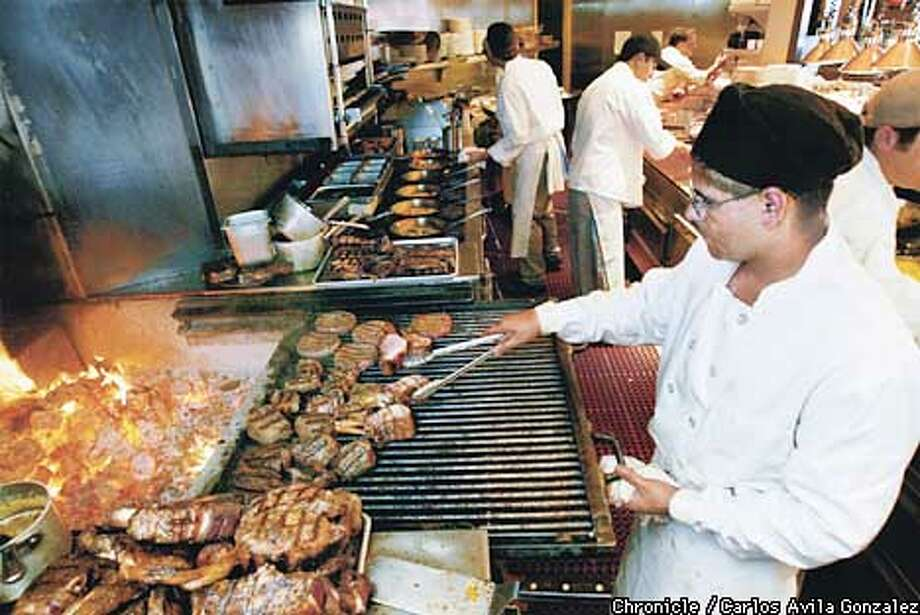 Jorge Ruiz cooks some grass-fed beef at ACME Chophouse at Pacific Bell Park in San Francisco, Ca., on Tuesday, June 18, 2002. The restaurant is one of the few in the city to serve the fine meats. (CARLOS AVILA GONZALEZ/SAN FRANCISCO CHRONICLE) Photo: CARLOS AVILA GONZALEZ