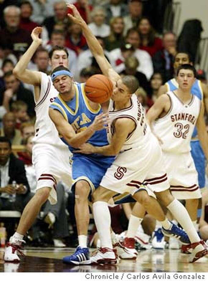 Stanford's Nick Robinson, right, and UCLA's Michael Fey, battle for a loose ball in the second half of the Cardinal's 67-52 victory over the Bruins at Maples Pavilion on Thursday, January 22, 2004, in Palo Alto, Ca. Event on 01/22/04 in Palo Alto, CA. Photo By Carlos Avila Gonzalez / The San Francisco Chronicle Photo: Carlos Avila Gonzalez