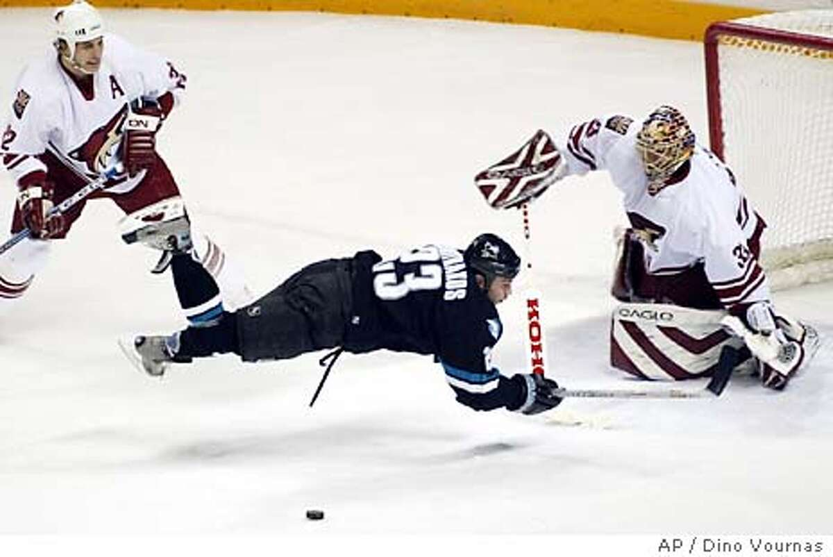 The San Jose Sharks' Niko Dimitrakos goes flying after being tripped up by the Phoenix Coyotes' Cale Hulse during the first period Thursday, January 22, 2004, in San Jose, Calif. Brian Boucher is in goal for the Coyotes. Hulse got two penalty minutes for the tripping. (AP Photo/Dino Vournas)