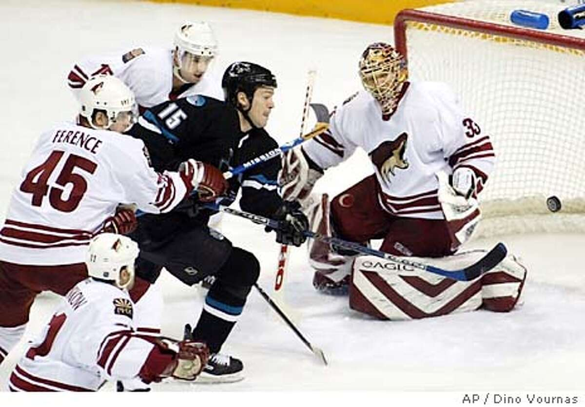 The San Jose Sharks' Wayne Primeau narrowly misses pushing a goal past Phoenix Coyotes goalie Brian Boucher during the first period Thursday, January 22, 2004, in San Jose, Calif. Coyote Brad Ference is on the left. Primeau scored a goal in the second period. (AP Photo/Dino Vournas)