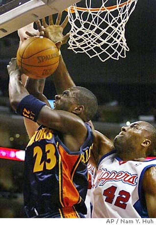 Golden State Warriors guard Jason Richardson, left, drives to the basket past Los Angeles Clippers forward Elton Brand during the first quarter Wednesday, Jan. 21, 2004, in Los Angeles. (AP Photo/Nam Y. Huh) Photo: NAM Y HUH