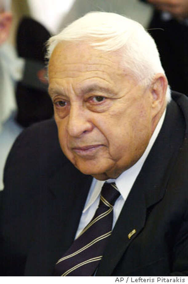 ** FILE ** Israeli Prime Minister Ariel Sharon pauses in this Jan. 19, 2004 file photo, prior to a meeting of the Foreign Affairs and Defense Committee of the Knesset, Israel's Parliament. An Israeli court on Wednesday Jan. 21, 2004, indicted an Israeli businessman on charges of bribing Sharon, further complicating the Prime Minister's clouded legal situation. (AP Photo/Lefteris Pitarakis) Photo: LEFTERIS PITARAKIS