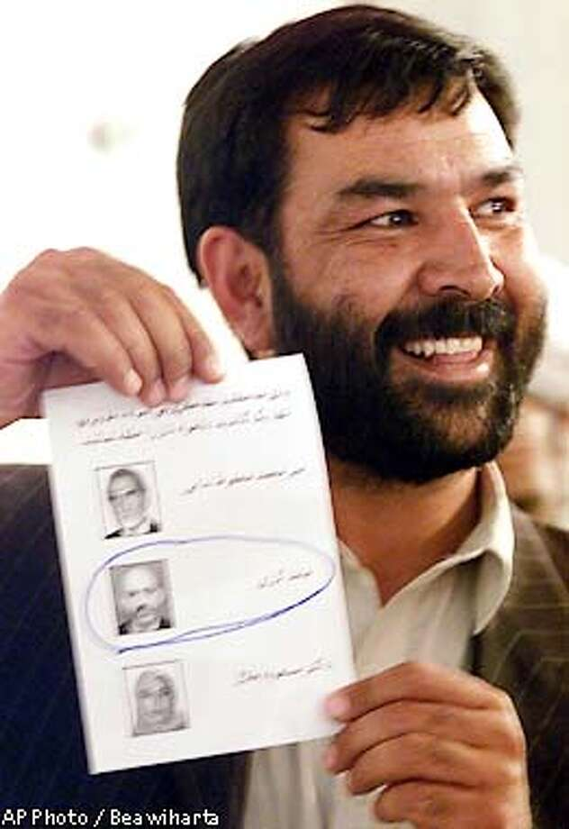 Afghan loya jirga (grand council) delegate shows his ballot with pictures of candidates for new Afghan leader, Mir Mohammad Mahfoz Hadoi, top, Hamid Karzai, center, marked, and Masooda Jalal, bottom, as he waits to vote, in Kabul Thursday, June 13, 2002. Hamid Karzai, a unifying figure during his interim tenure at the head of the U.S.-backed Afghan administration, was overwhelmingly elected head of state Thursday by the loya jirga. (AP Photo/Beawiharta, Pool) Photo: BEAWIHARTA