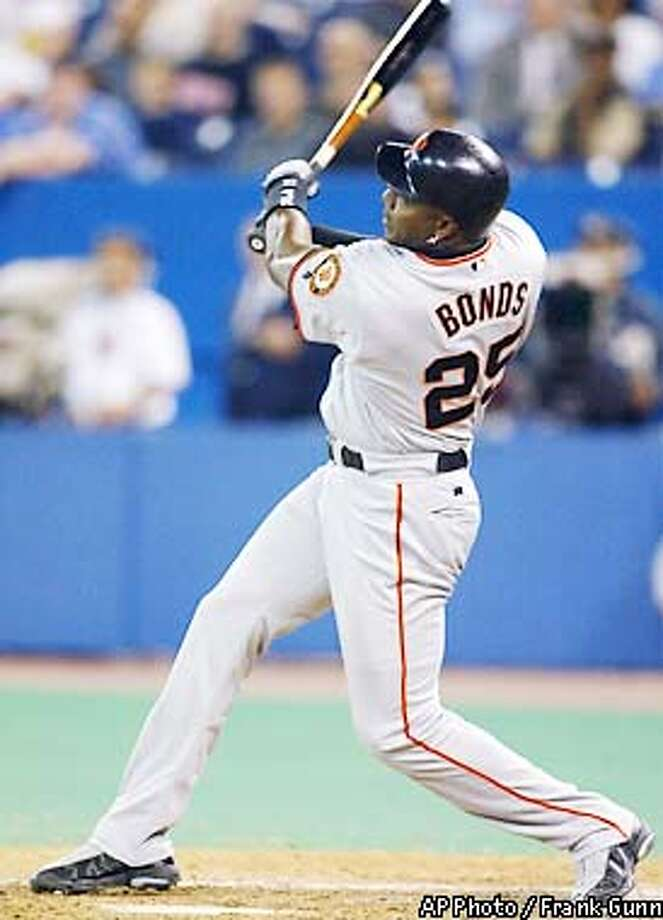 San Francisco Giants Barry Bonds watches as his home run off Toronto Blue Jays Cliff Politte soars over the fence during ninth inning interleague action in Toronto Wednesday, June 12, 2002. (AP Photo/CP, Frank Gunn) Photo: FRANK GUNN