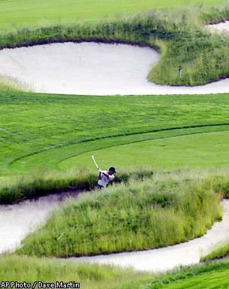 Tiger Woods hits from the bunker on the sixth hole Tuesday, June 11, 2002, at the U.S. Open Golf Championship at the Black Course of Bethpage State Park in Farmgindale, N.Y. (AP Photo/Dave Martin) Photo: DAVE MARTIN