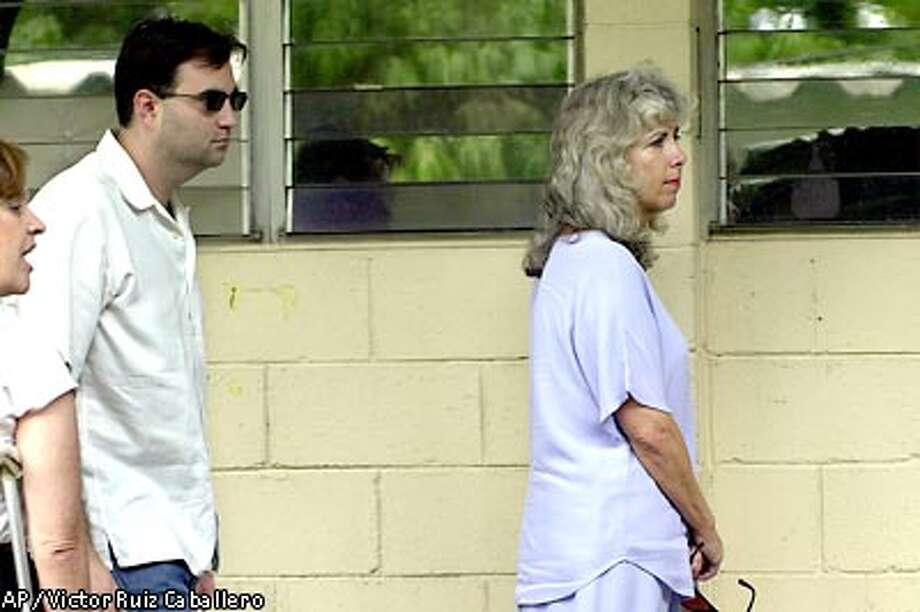 The wife, right, and son of killed American Mauricio Gonzalez, arrive at the medical examiners office in San Salvador, El Salvador Thursday June 13, 2002, where an autopsy of Gonzalez's body will take place. According to police, Gonzalez's body was found Thursday in a well near his home on El Salvador's Pacific coast. Person at right is unidentified. ( AP Photo/Victor Ruiz Caballero) Photo: VICTOR RUIZ CABALLERO