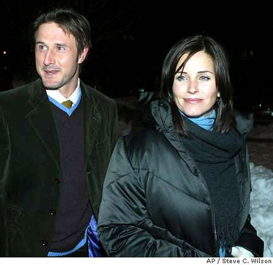 "SPECIAL TO THE SAN FRANCISCO CHRONICLE--Actress Courtney Cox, right, and actor husband David Arquette arrive for the film ""November"" at the Library CenterTheatre during the Sundance Film Festival Saturday, Jan. 17, 2004 in Park City, Utah. Cox plays a starring role in the film. (AP Photo/Steve C. Wilson) ROUTE TO CAFRA LANCE IVERSON AUTHORIZING Photo: STEVE C. WILSON"