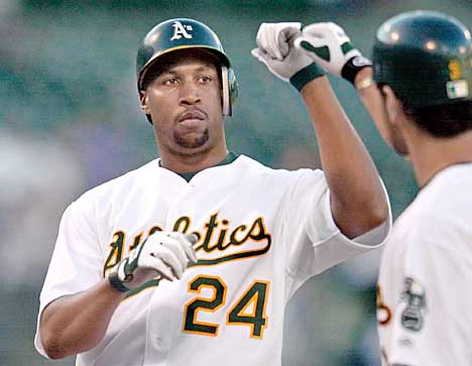 Oakland Athletics' Jermaine Dye, left, is greeted by Eric Chavez at home plate after hitting a three-run home run against the Milwaukee Brewers during the first inning Monday, June 10, 2002 in Oakland, Calif. (AP Photo/Julie Jacobson) Photo: JULIE JACOBSON