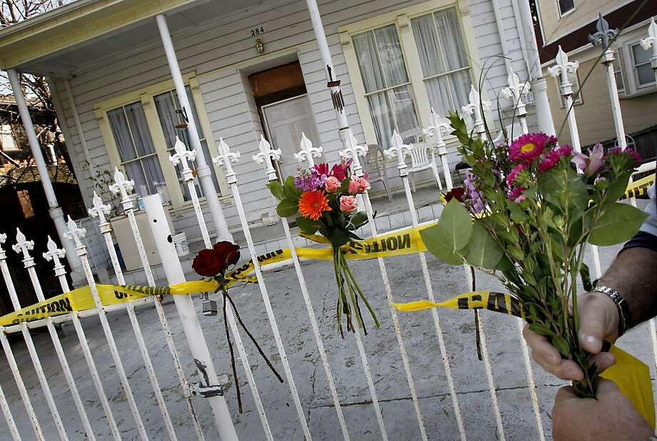 Family friend Mike Arrajj held flowers he would attach to the fence with tape from the investigation. Friends and family members returned to the home at 284 Athol Avenue in Oakland, Calif. Sunday January 29, 2012 where two parents were allegedly killed by their son late last week. Photo: Brant Ward, The Chronicle