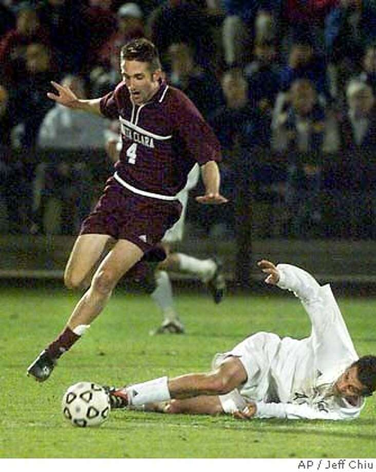 SOCCER24B-C-23NOV01-SP-JC-- Santa Clara University's Ryan Cochrane has to leap over Cal's fallen Patrick Fisher to maintain control of the ball as SCU beat Cal 1-0 in the second overtime of the first round of the NCAA soccer tournament at Maloney Field at Stanford on Friday evening. Photo by Jeff Chiu / The Chronicle. CAT Photo: Jeff Chiu