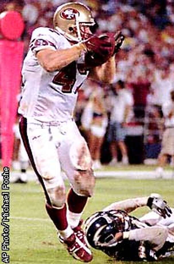 San Francisco 49ers' Steve Avery scores a touchdown on a four-yard pass from quarterback Jeff Brohm in the fourth quarter of their 20-13 loss to the San Diego Chargers Saturday, Aug. 2, 1997 in San Diego. Chargers' Gerome Williams is on the ground. (AP Photo/Michael Poche)