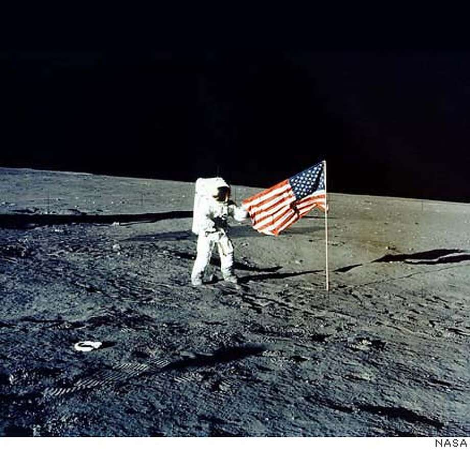 "WAS03: :WASHINGTON,9JUL99 - Charles ""Pete"" Conrad Jr. stands with the American flag on the lunar surface during the Apollo 12 mission, 1969. Conrad, the third man to walk on the moon from the Apollo 12 mission, died July 8 in Ojai, California at the age of 69 from injuries resulting from crashing his Harley-Davidson motorcycle. bm/NASA Photo REUTERS Photo: NASA"
