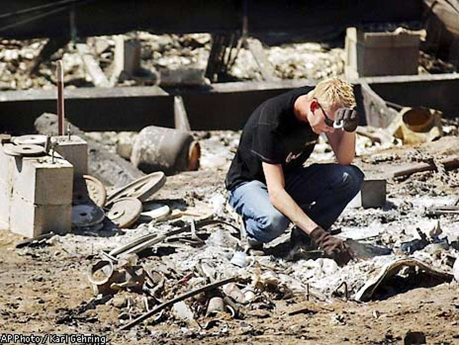 Derrike Hubbs picked through the remains of his belongs Tuesday, June 11, 2002, he had stored in a shed next to his home in Glenwood Springs, Colo., both of which were destroyed by the Coal Seam fire. (AP Photo/Denver Post, Karl Gehring) Photo: KARL GEHRING