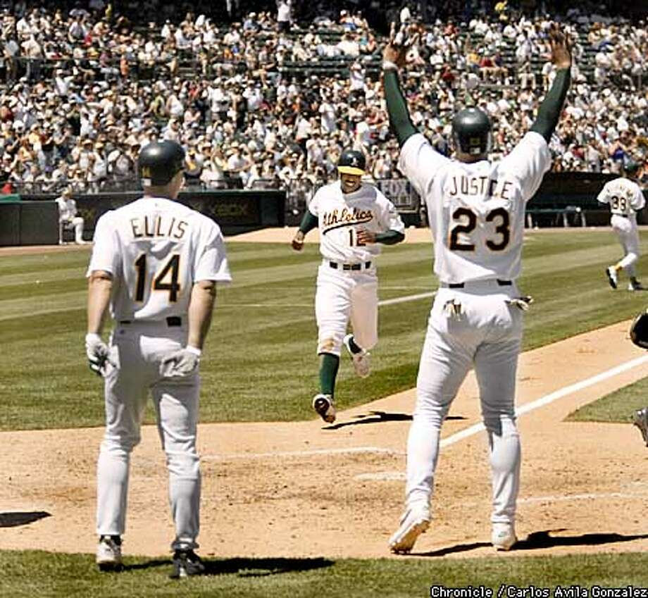 David Justice, right, Mark Ellis, left, wait to congratulate, Terrence Long at the plate as he scores in the bottom of the fourth inning, part of a six run fourth inning for the Athletics, at Network Associates Coliseum on Sunday, June 9, 2002, as the A's played the Houston Astros. (CARLOS AVILA GONZALEZ/SAN FRANCISCO CHRONICLE) Photo: CARLOS AVILA GONZALEZ