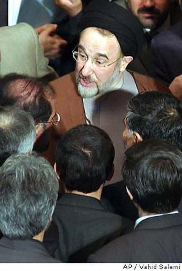 Iranian reformist President Mohammad Khatami, top, talks with lawmakers during an open session of parliament, in Tehran, Iran, Wednesday, Jan. 14, 2004. Khatami told 27 provincial governors Tuesday who threatened to resign that he may join their walkout unless conservatives reverse a decision barring pro-reform candidates from elections. The hard-line Guardian council, an unelected constitutional watchdog, has barred more than 3,000 candidates _ including over 80 sitting lawmakers _ from standing in the Feb. 20 elections. Lawmakers say the disqualified are all reformists. (AP Photo/Vahid Salemi) Photo: VAHID SALEMI