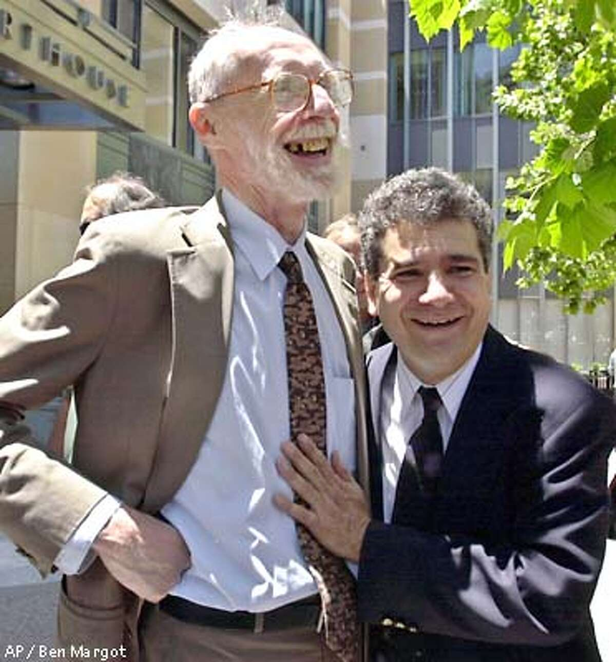 Darryl Cherney, right, hugs his lead attorney Dennis Cunningham Tuesday, June 11, 2002, in Oakland, Calif. Twelve years after they were arrested in the bombing of their own car, two Earth First! activists were awarded $4.4 million Tuesday in a federal suit claiming they were framed by Oakland police and FBI agents. After 17 days of deliberations, jurors awarded the money to activist Darryl Cherney and the estate of Judi Bari, who died of cancer in 1997. (AP Photo/Ben Margot)