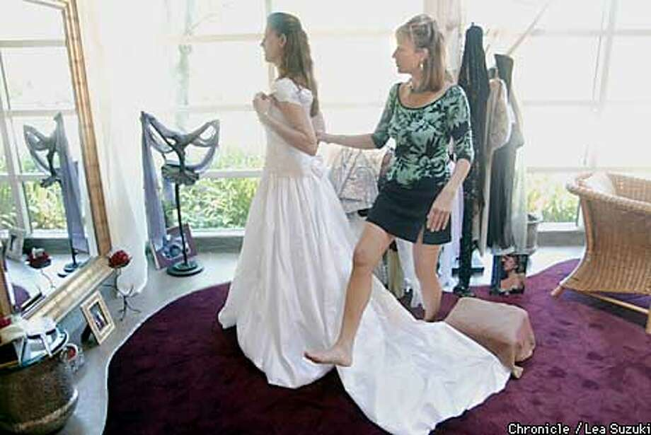 Tammie Hope of Walnut Creek inspects herself in the mirror as Cera Jane of Cera Jane's in Corte Madera checks the fit of the wedding dress. Chronicle photo by Lea Suzuki
