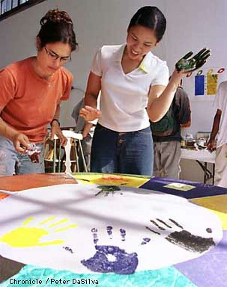 Patricia Ancheta, 16, reacts to her impresion of her hand on a group table project as Mission Teens Art Project intern Sequoiah Wachenheim works on her section of the table. Each section of the table represents each students own personality with their hand print and personlized artwork. Chronicle Photo By: Peter DaSilva Photo: PETER DASILVA