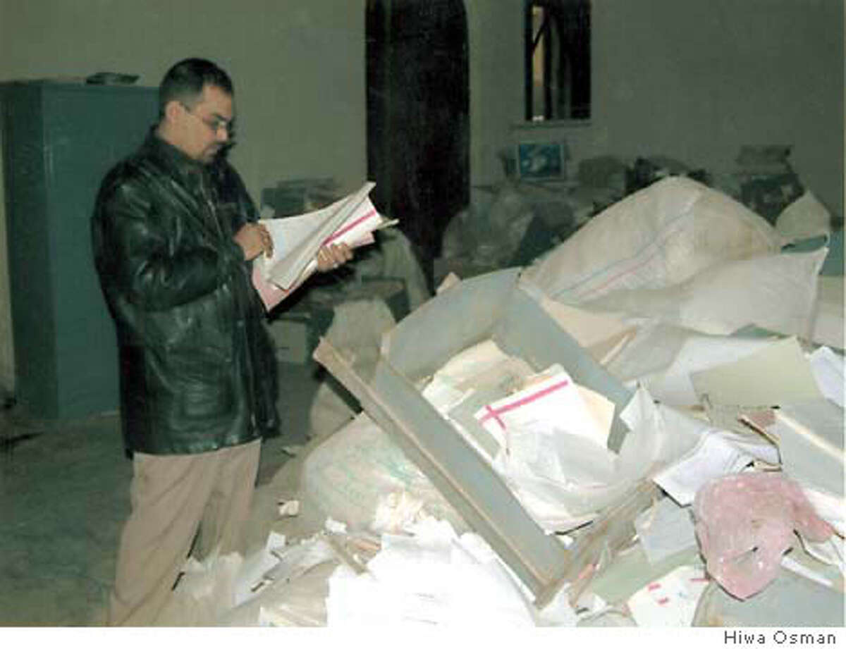 Inspectors search through piles of death warrants personaly signed by Saddam Hussein.